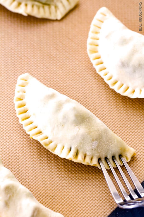 Mexican Chicken Empanadas stuffed and being sealed closed with a fork before cooking