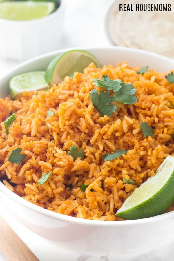 mexican rice recipe in a bowl garnished with cilantro and lime wedges