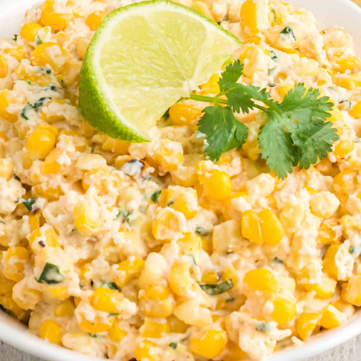 square close up image of mexican street corn dip in a bowl topped with cilantro and a lime wedge