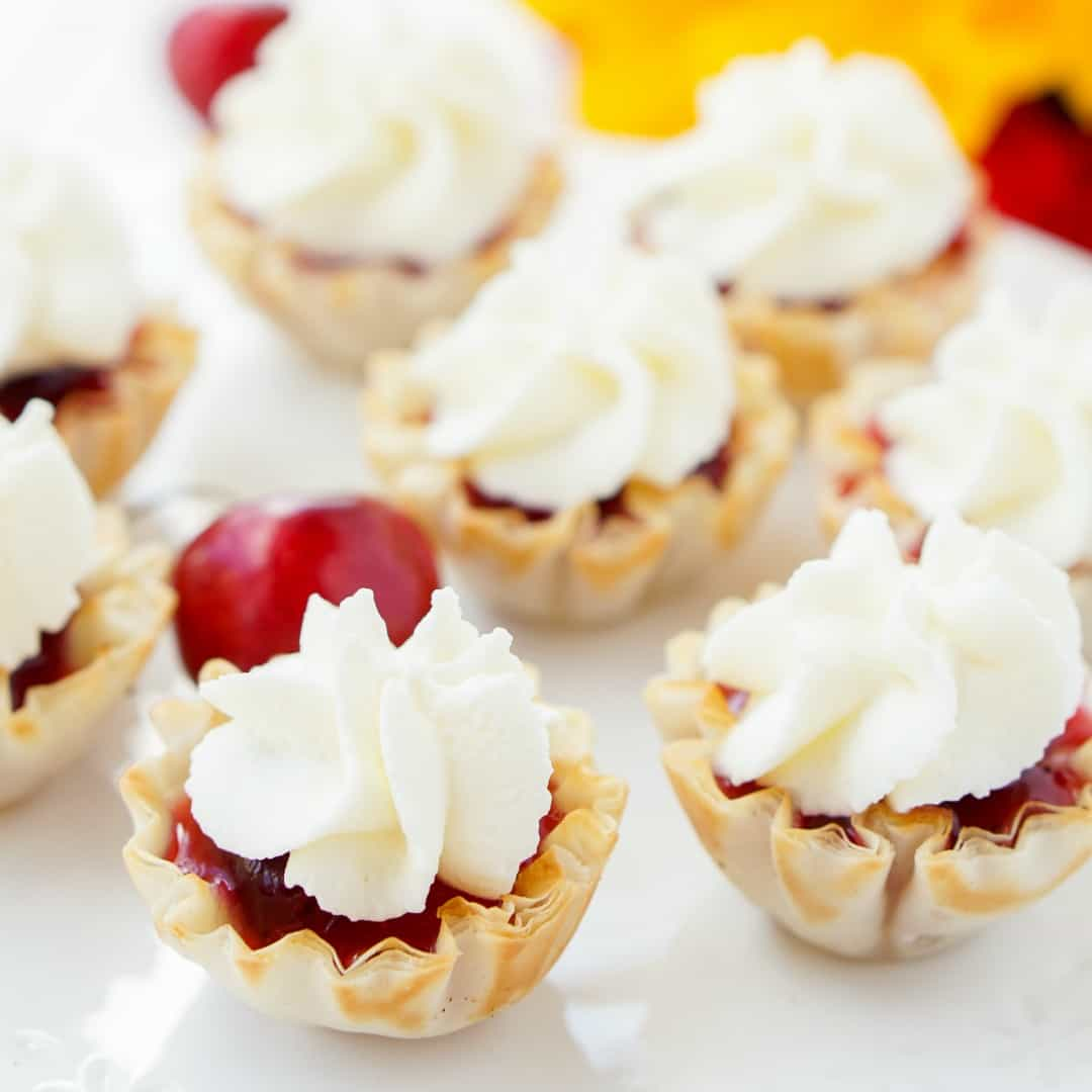 Mini Cherry Pie Bites have everything I look for in a recipe: deliciousness, simplicity, versatility, and of course, sugar! These tasty little treats are the perfect pint-sized dessert to enjoy this summer.
