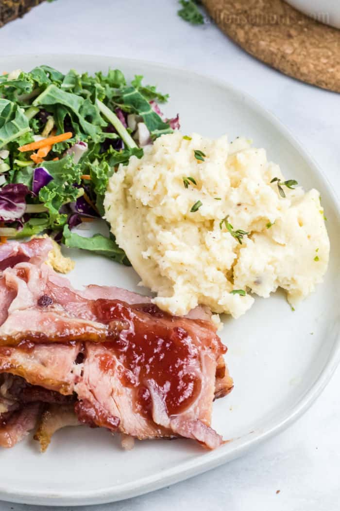 mashed potatoes on a dinner plate with ham and salad