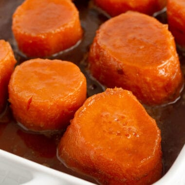 square image of candied yams in a baking dish with the sauce