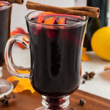 Image of a clear glass filled with Mulled wine with orange slices and a cinnamon sticks on top