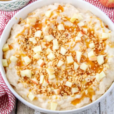 square image of apple cheesecake dip in a shallow bowl garnished with caramel, nuts, and apples