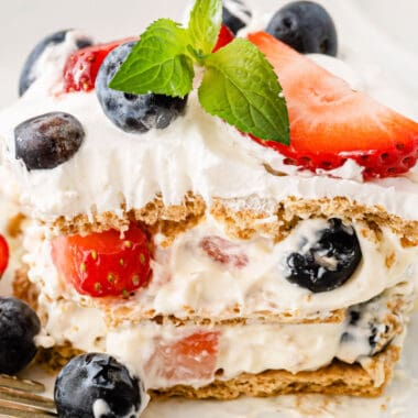 squar eimafe of a berry icebox cake slice with a sprig of mint on top