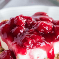 close up image of a slice of no bake cherry cheesecake on a white plate.