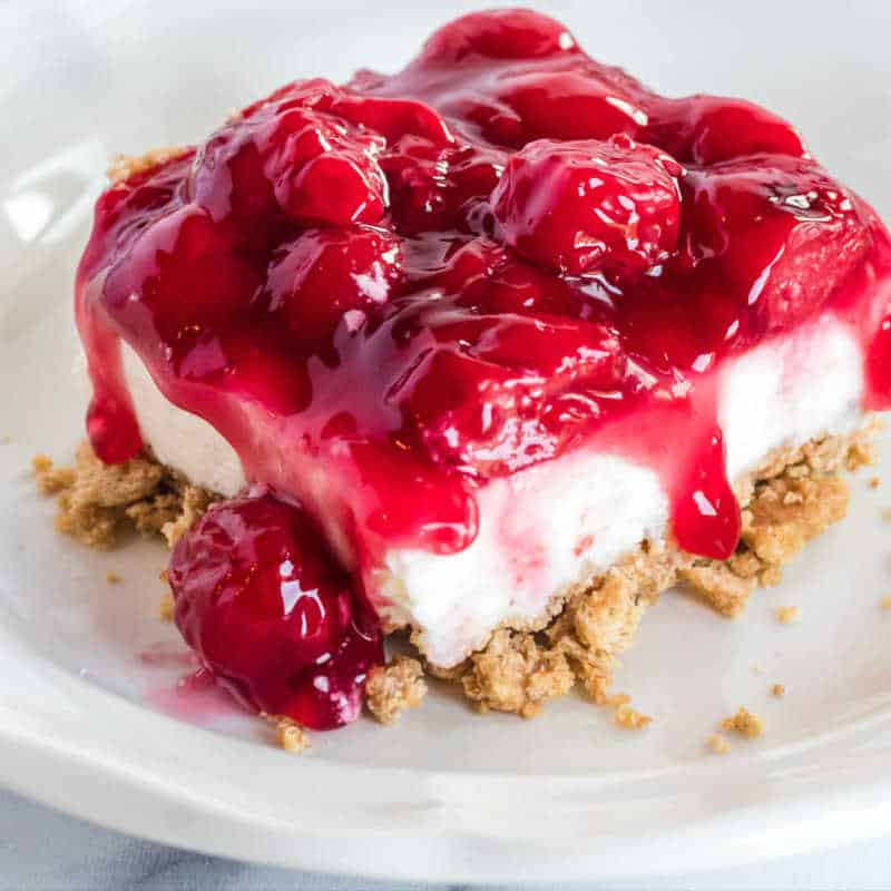 cheesecake on a white plate with cherry topping and graham cracker crust.