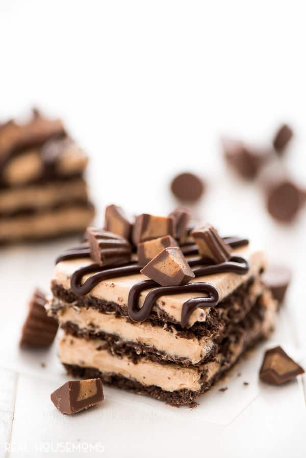 A slice of No-Bake Peanut Butter Icebox Cake topped with chocolate peanut butter ganache and chopped Reese's peanut butter cups
