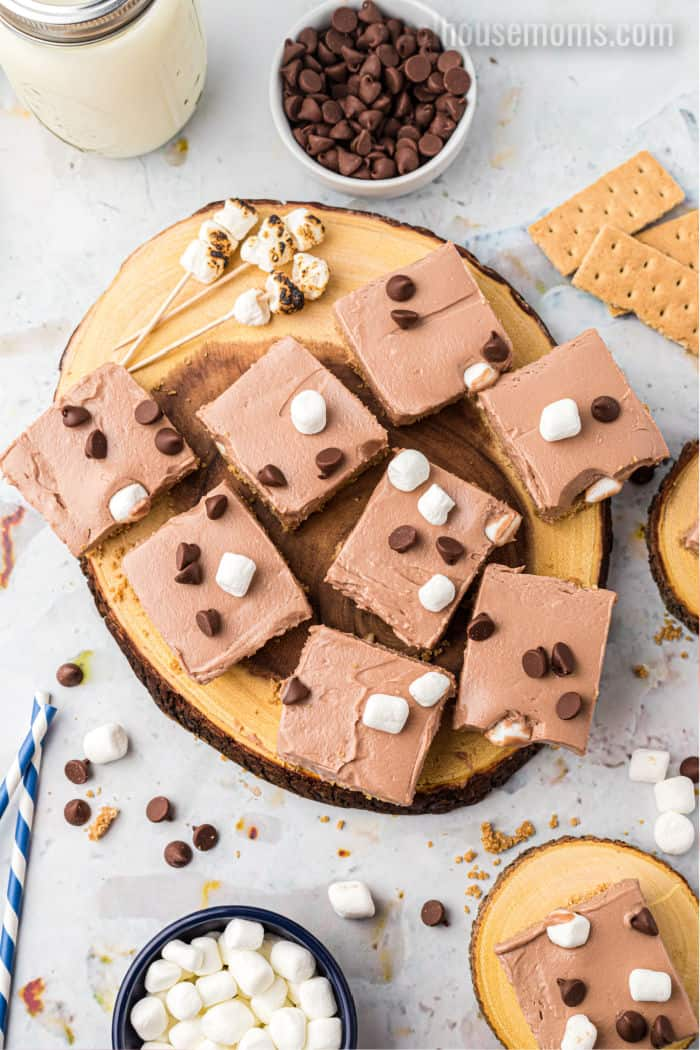 platter of no bake s'more cheesecake bars topped with mini marshmallows and chocolate chips