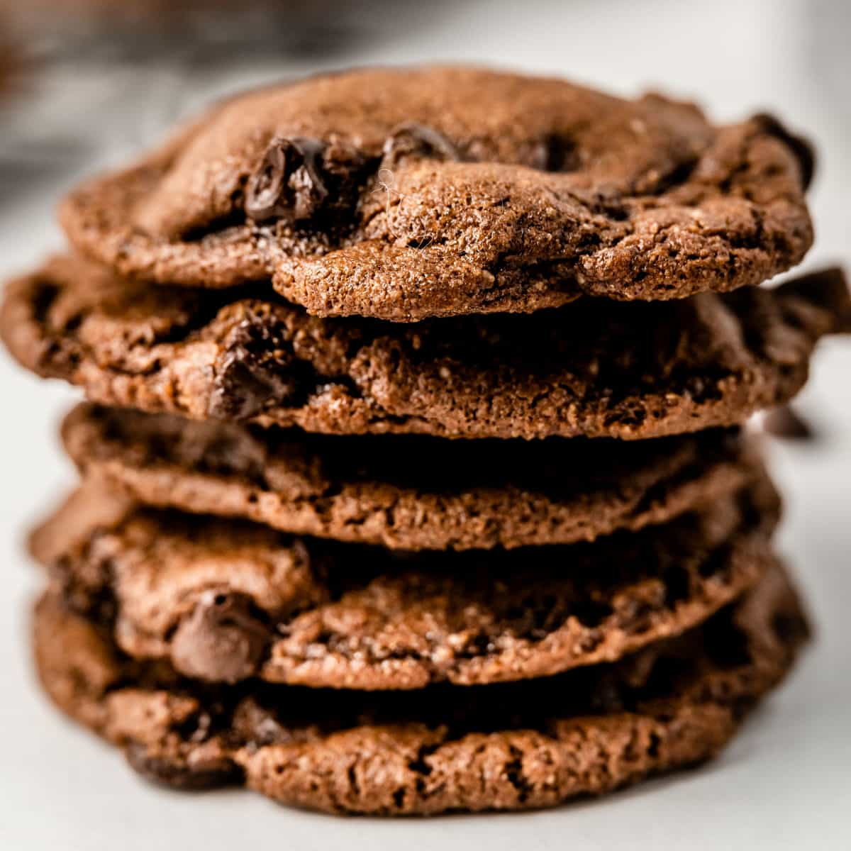 square image of a stack of nutty triple chocolate cookies
