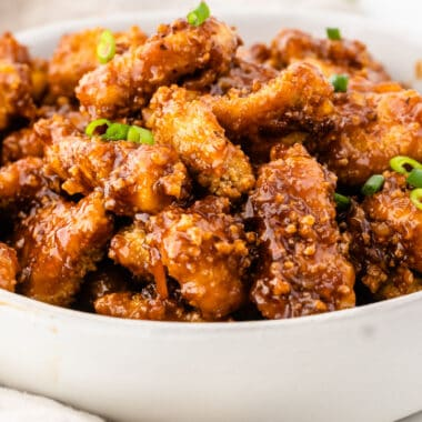 square image of orange chicken in a white serving bowl