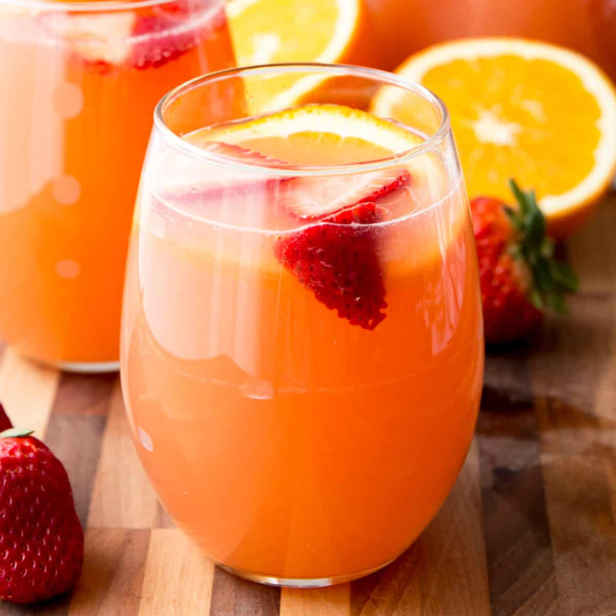 square image of orange strawberry rose sangria on a cutting board in a stemless wine glass