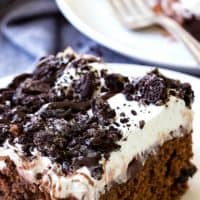 Oreo Poke Cake is an easy dessert recipe that satisfies your sweet tooth! Chocolate cake topped with pudding, Oreos, whipped cream and chocolate syrup is always a win!