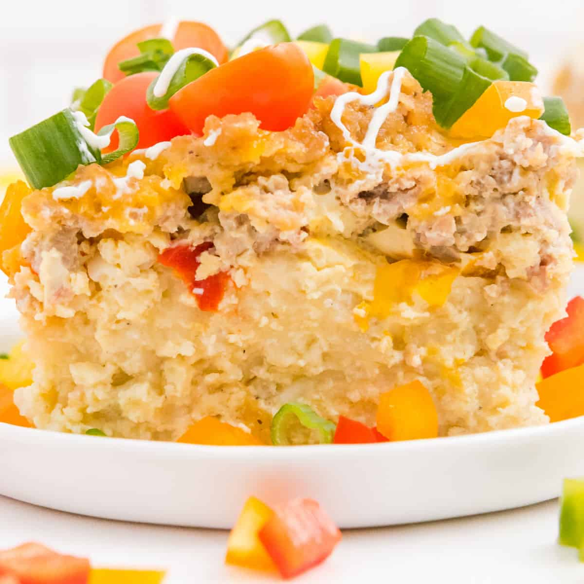 square image of overnight crock pot breakfast casserole on a plate topped with tomatoes and green onion