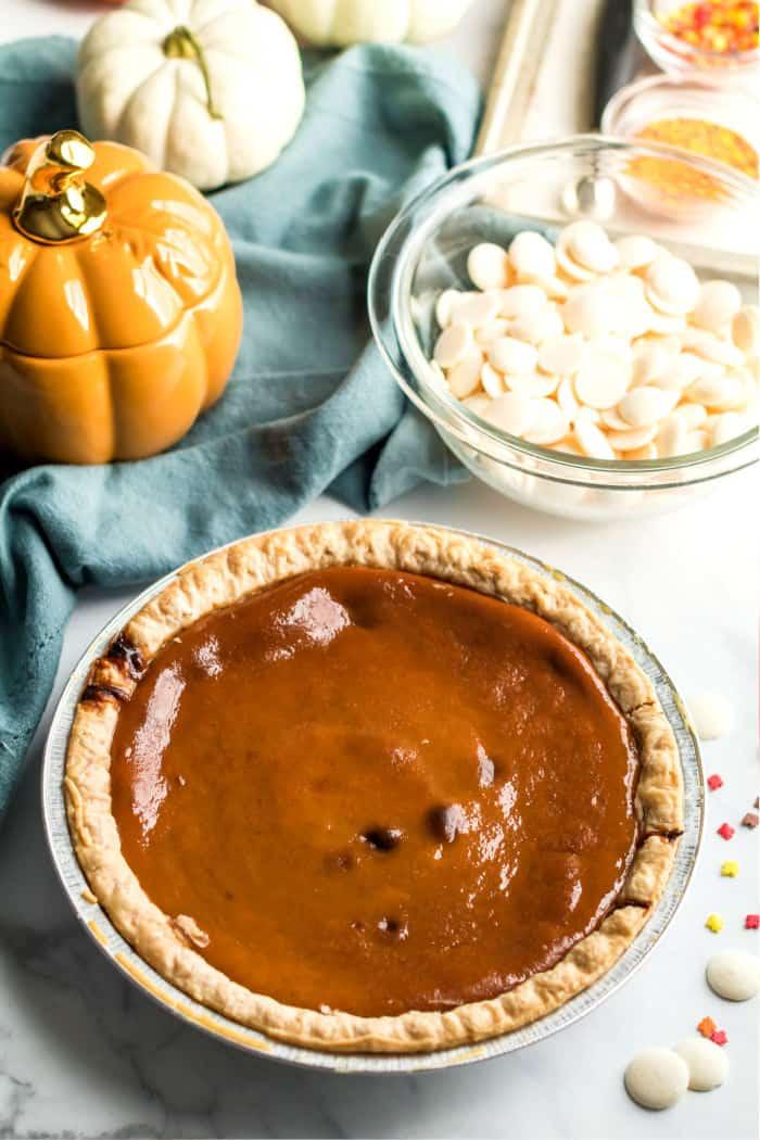 pumpkin pie next to a bowl of candy melt chips