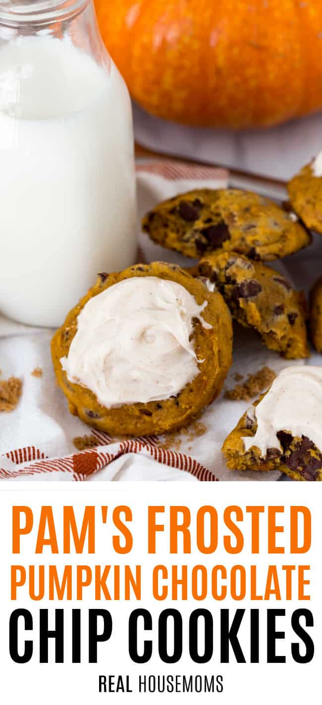 frosted pumpkin cookie next to a plate of cookies, a bottle of milk, and a pumpkin