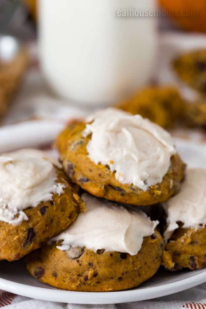 frosted pumpkin chocolate chip cookies on a plate next to a bottle of milk