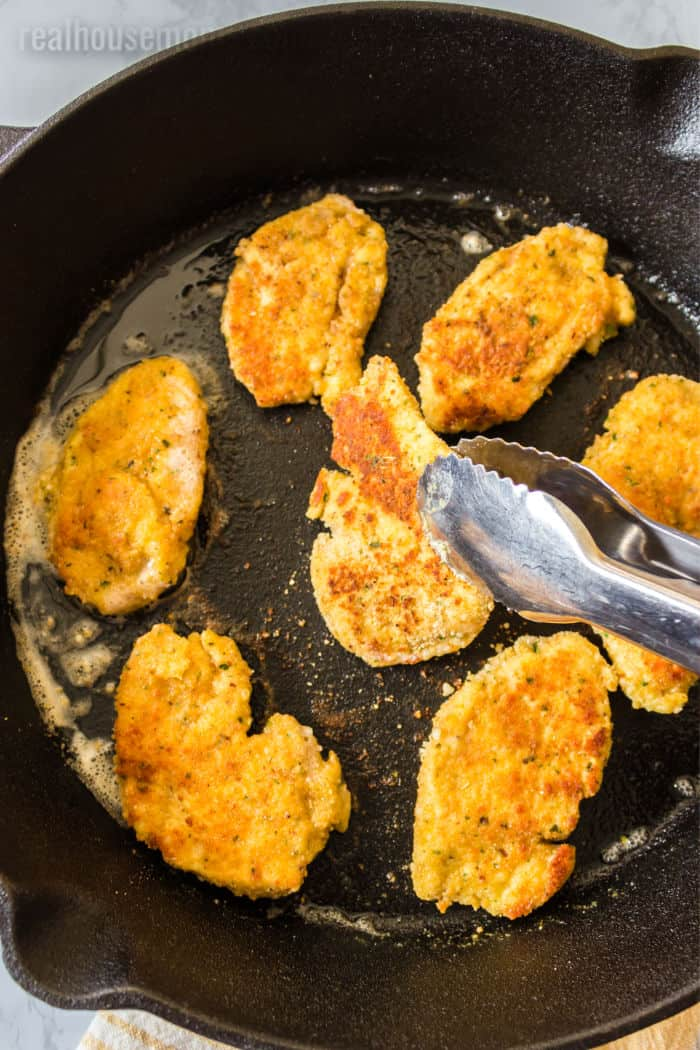 parmesan breaded chicken tenders being fried in a skillet