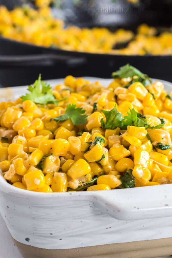 close up of parmesan cilantro corn in a serving dish