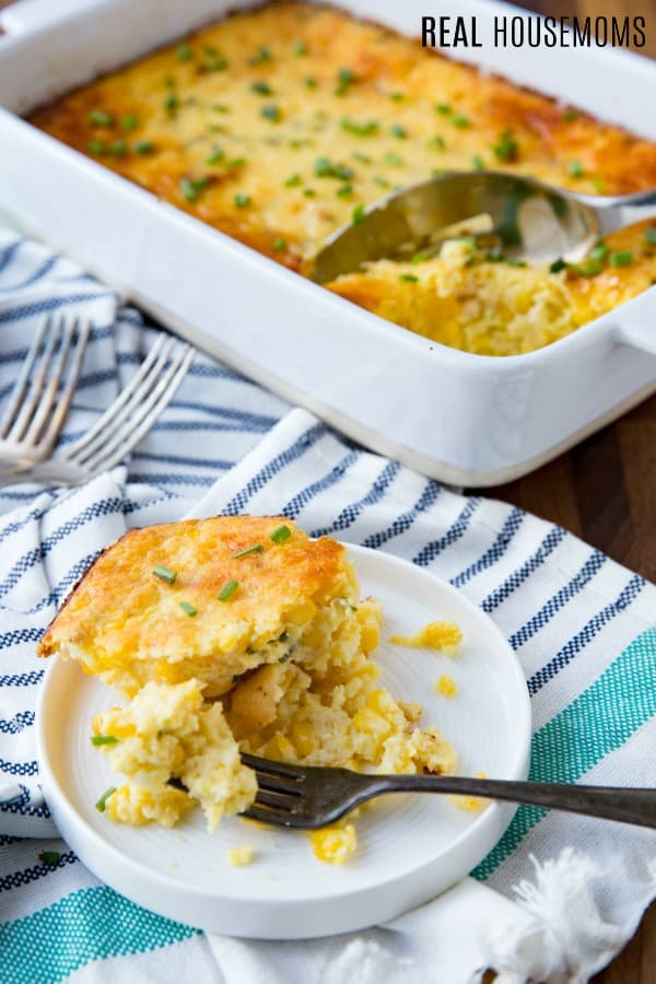 parmesan corn casserole served on a plate with the baking dish in the background