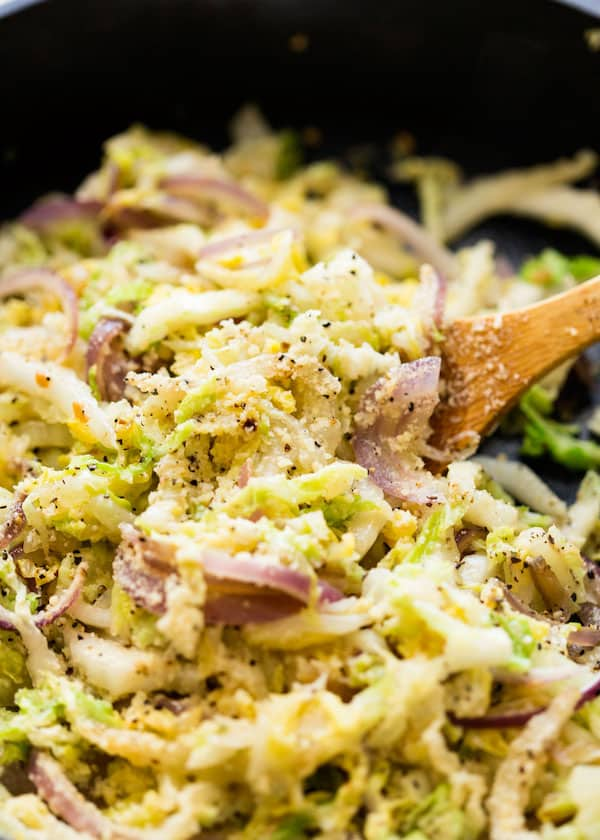 Spoonful of Parmesan Garlic Cabbage being lifted from the skillet