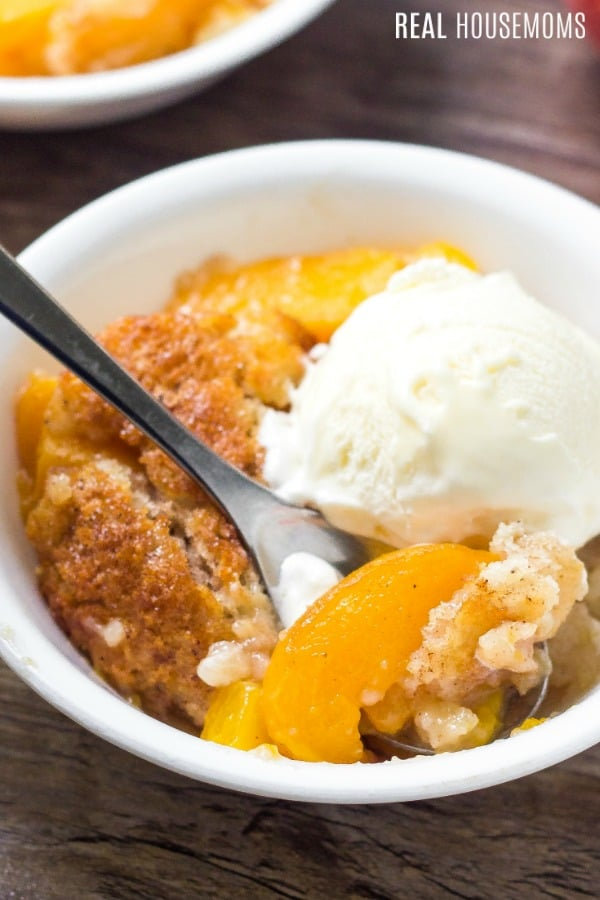 peach cobbler in a bowl with ice cream and a spoon