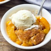 This easy Peach Cobbler Recipe is the perfect summer dessert. With juicy peaches, a hint of cinnamon, and fluffy vanilla cake - it's the best peach cobbler around!