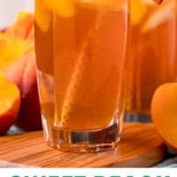 glass of peach iced tea with a straw and peach slice for garnish with recipe name at bottom