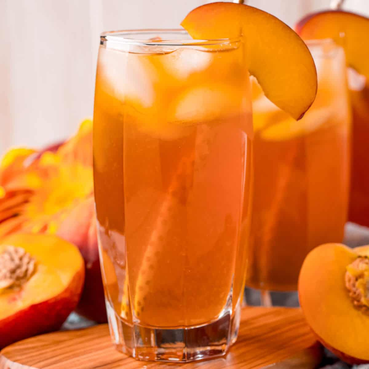 square image of two glasses of peach iced tea with a peach slice for garnish