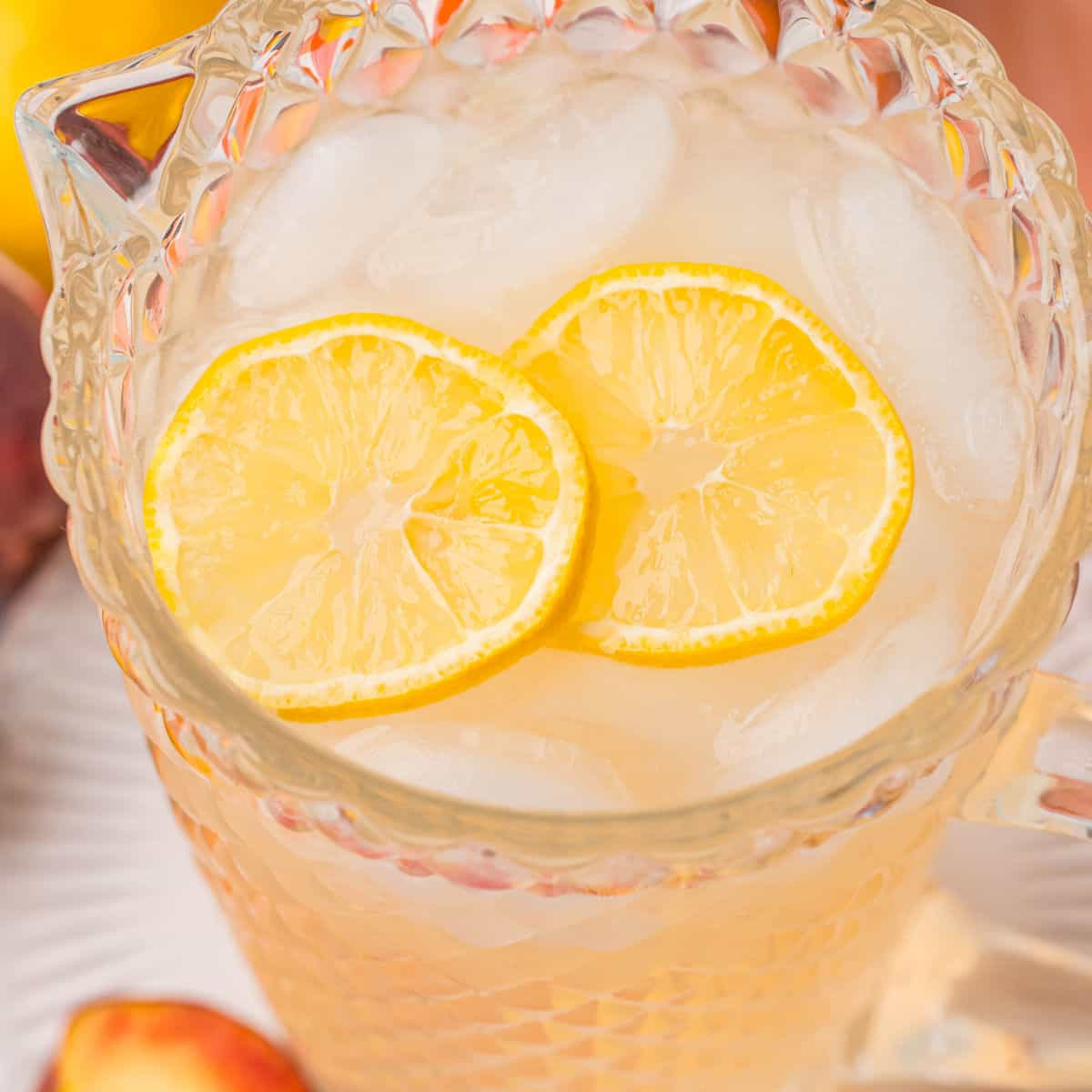 square image looking down into a pitchers of peach lemonade with lemon slices floating on top