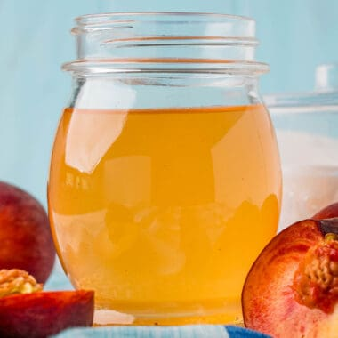 square image of peach simple syrup in a jar next to peaches