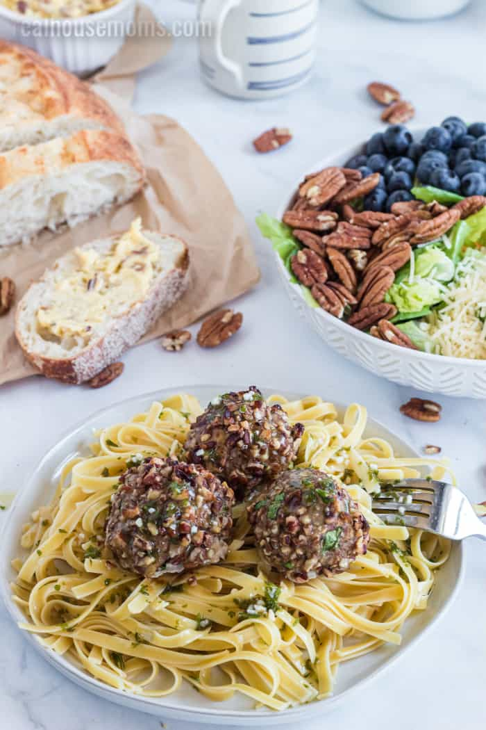 pecan chicken meatballs over pasta served with bread and a salad