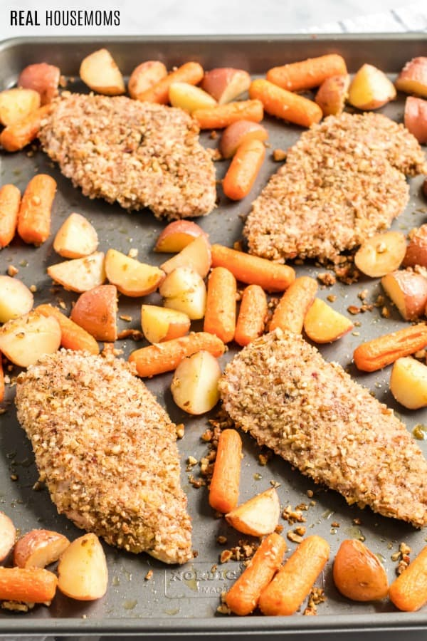pecan chicken with potatoes and carrots on a baking sheet