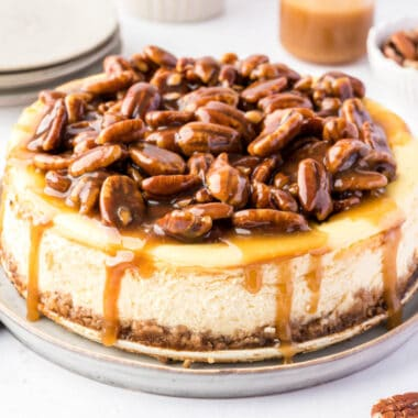 square image of a pecan pie cheesecake with caramel sauce dropping down the sides