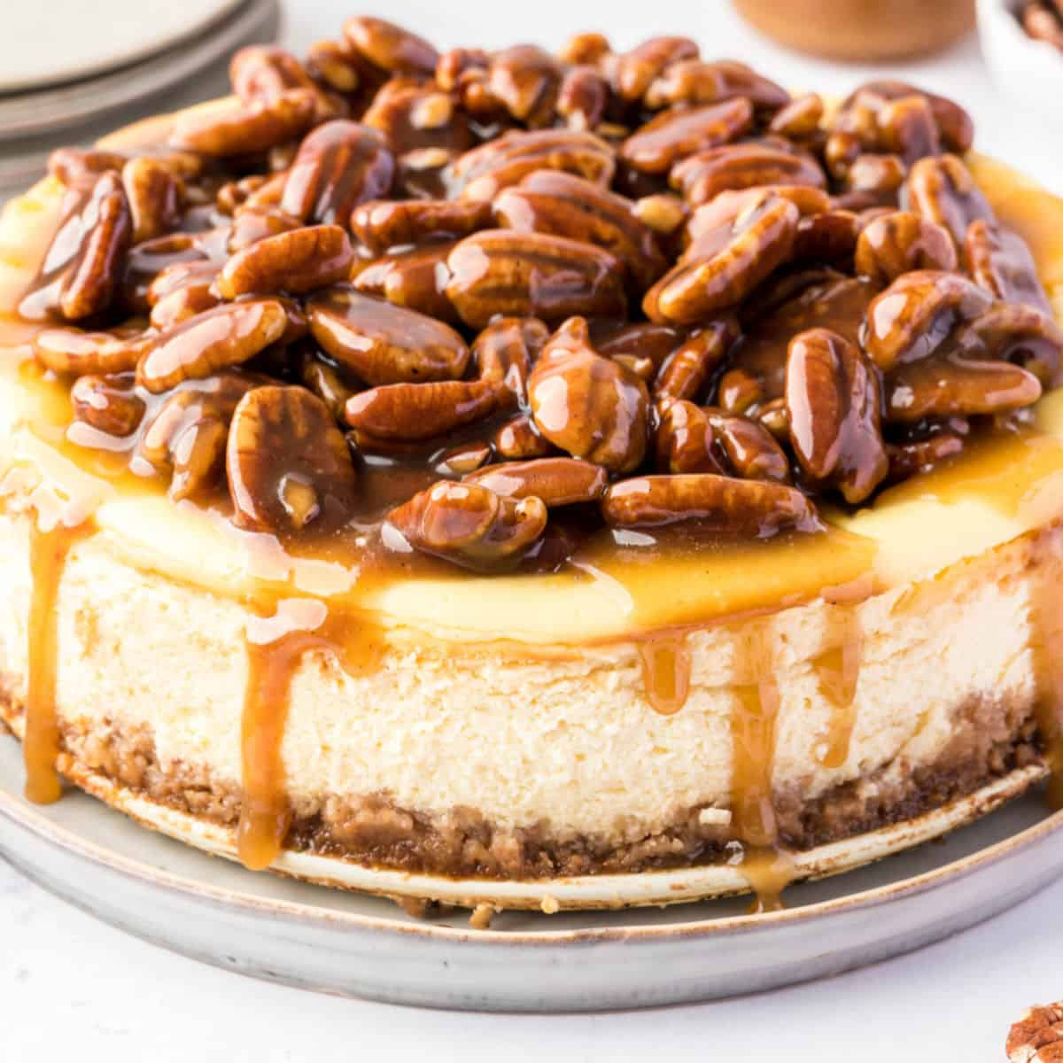 square image of a whole pecan pie cheesecake with caramel sauce dropping down the sides