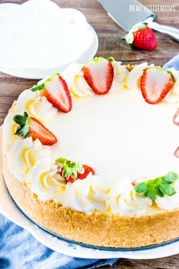 perfectly easy no bake cheesecake with whipped cream and strawberries