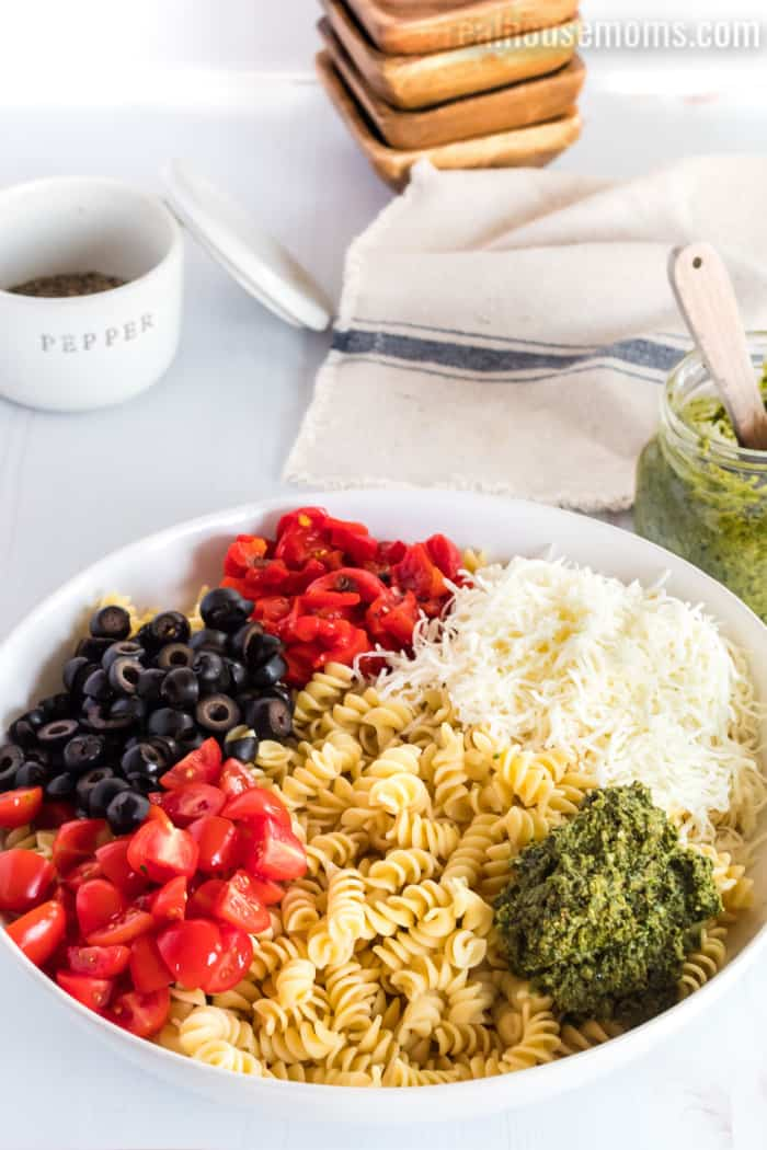 ingredients for pesto pasta salad in a bowl with cooked pasta