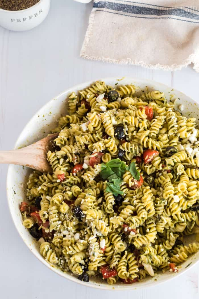 pesto pasta salad in a bowl with a wooden spoon