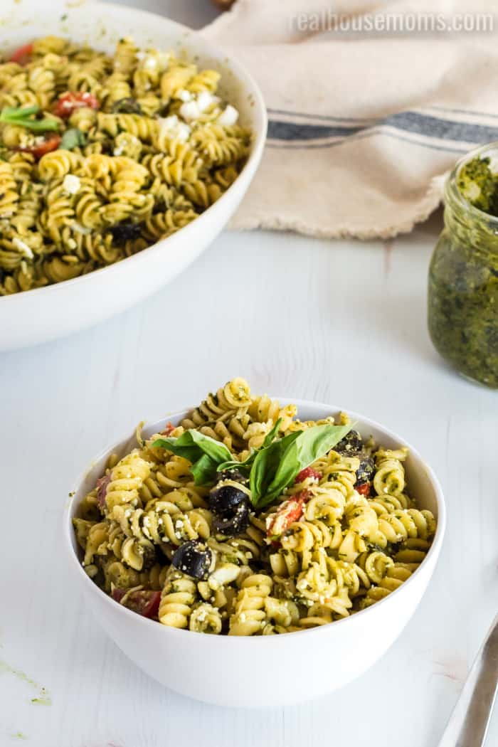 pesto pasta salad served in a bowl with basil on top