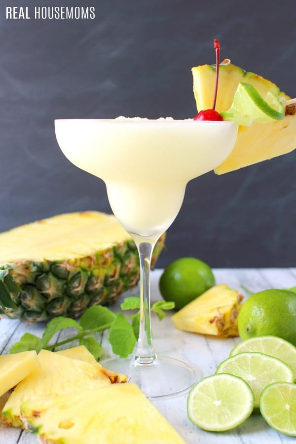 Pina colada rum cocktail with pineapple and lime slices