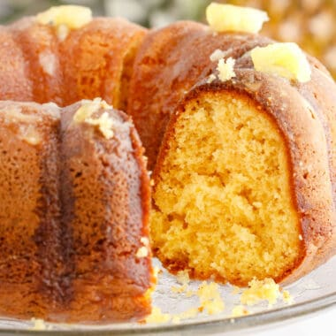 square image of pineapple bundt cake with a slice removed to show the cake crumb