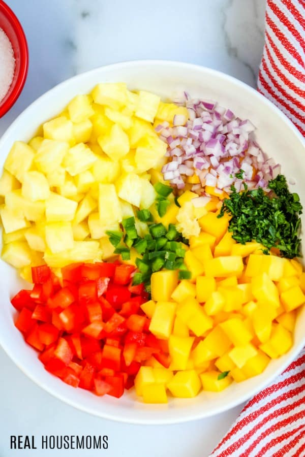 pineapple mango salsa ingredients in a mixing bowl