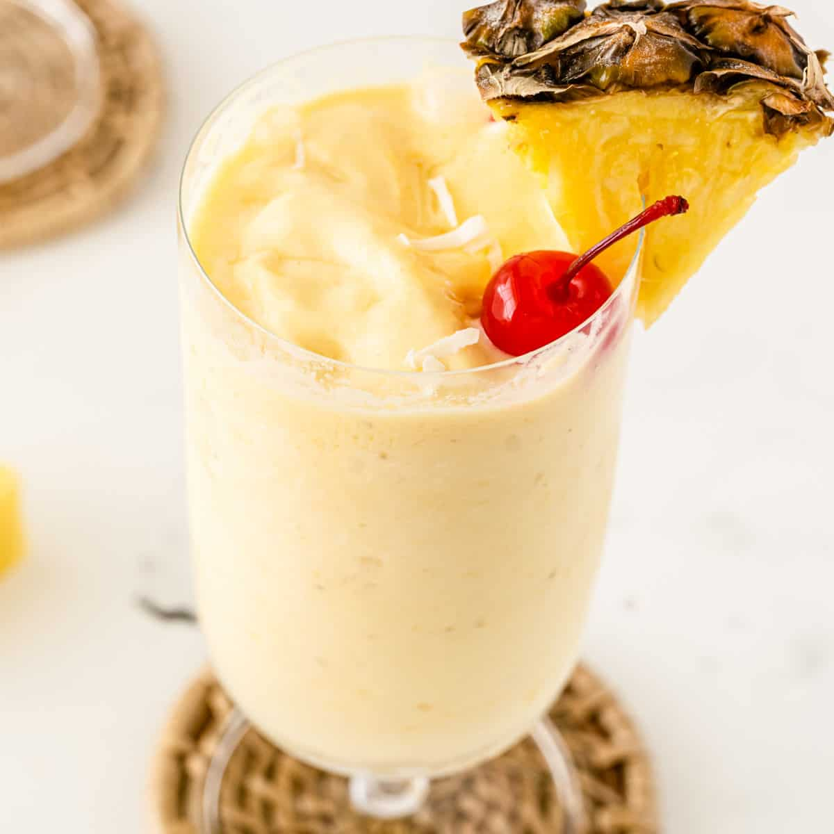 square image of a pineapple rum slushie garnished with a cherry, coconut flakes, and a wedge of pinepple