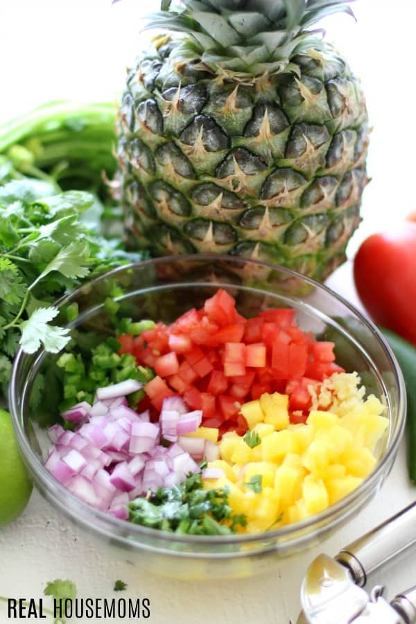 fresh pineapple salsa ingredients diced, in a mixing bowl, ready to be stirred