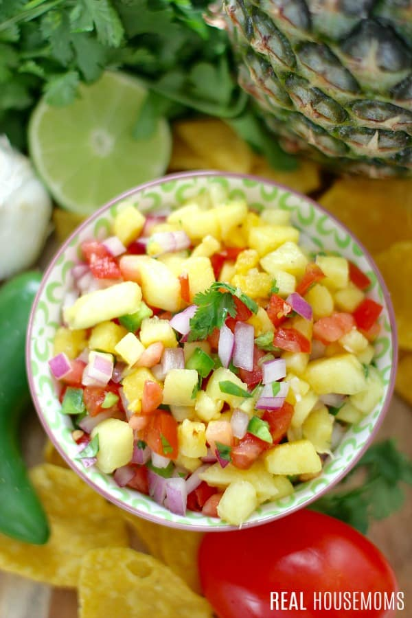 fresh pineapple salsa in a dip bowl with fresh ingredients behind it