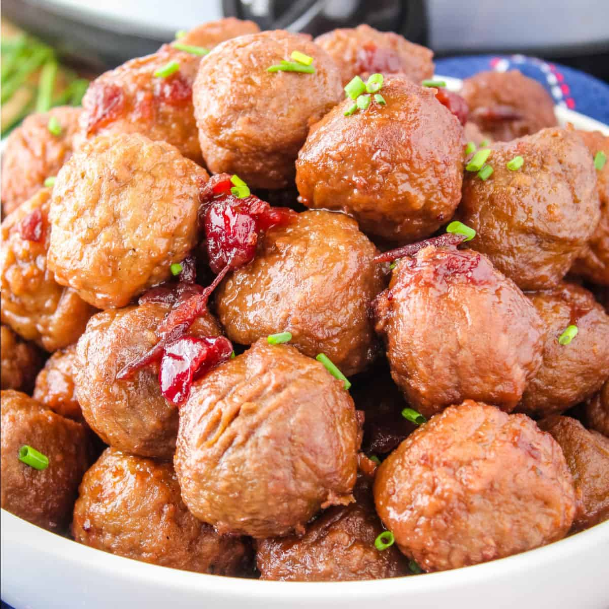 square image of pinot noir & cranberry meatballs piled up in a serving bowl with chopped chives for garnish