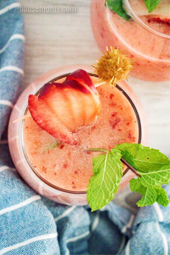 looking down into a glass of frozen peach margarita with fruit and mint for garnish