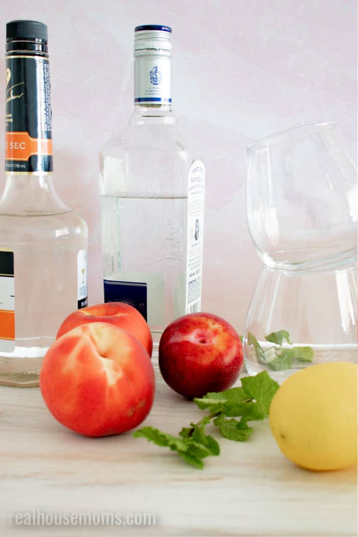 bottle of booze, fresh peaches, plums, and mint next to empty glasses