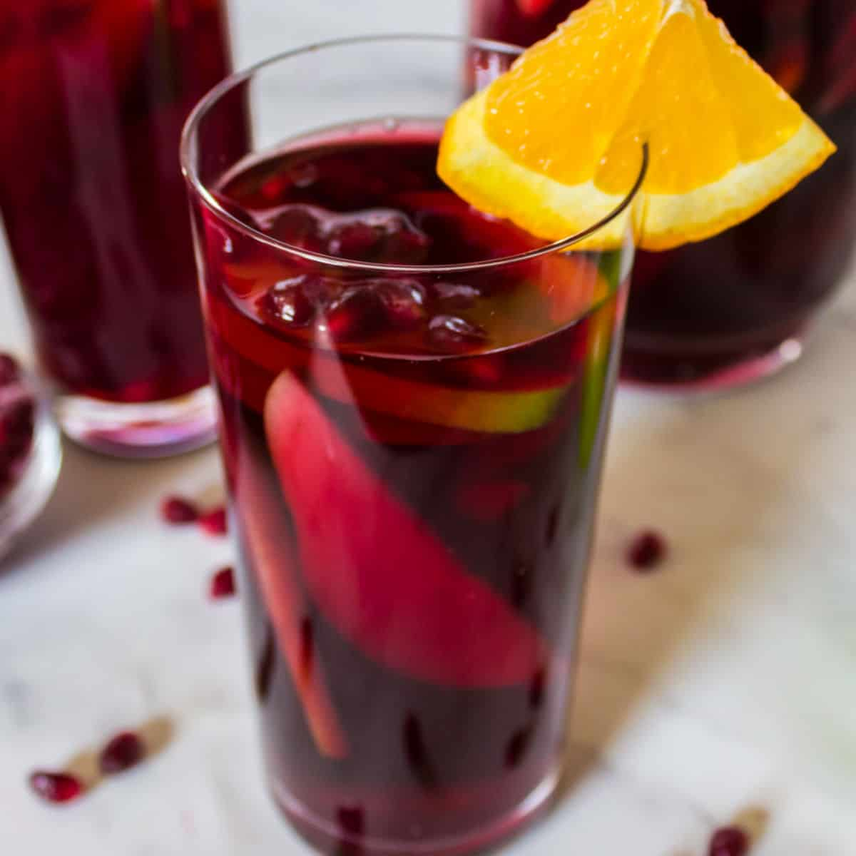 square image of pomegranate sangria in a tall glass with orange wedge and pomegranate arils
