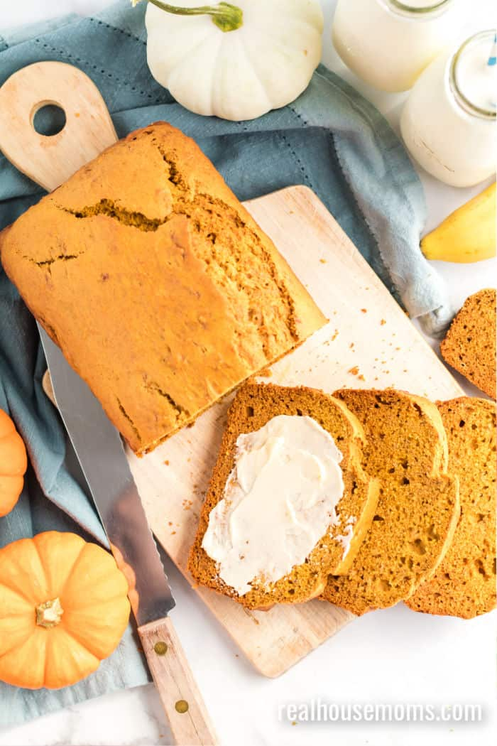 loaf of banana bread cut into slices with one slice buttered